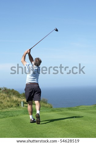 Senior male golfer playing golf from the tee box on a beautiful summer day next to the ocean - stock photo