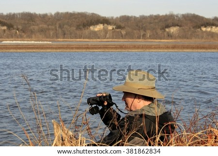 Senior male in a wide-brimmed hat watching white pelicans across the lake - stock photo