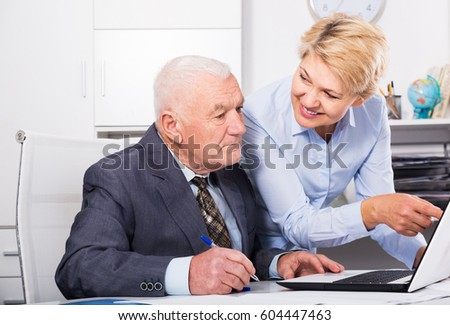 Senior male manager and female secretary working productively together in office