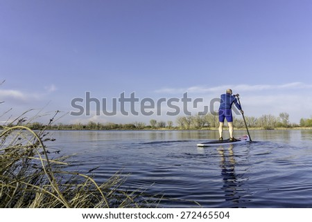 Senior male on stand up paddling (SUP) board. Early spring on calm lake in Fort Collins, Colorado.. - stock photo