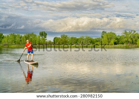 senior male on stand ups paddleboard - calm lake under stormy sky, springtime scenery in Colorado - stock photo