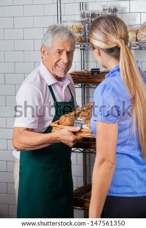 Senior male owner assisting female customer in buying muffins at supermarket