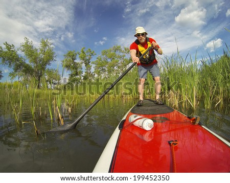 senior male paddler enjoying workout on stand up paddleboard (SUP), calm lake in Colorado, spring colors - stock photo