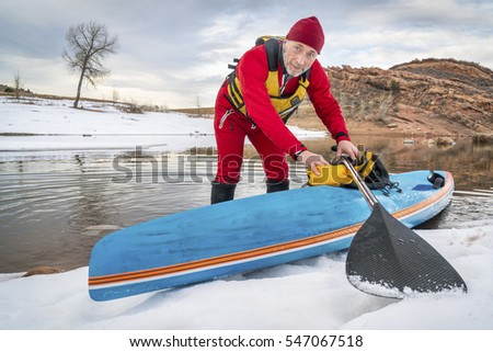senior male paddler in drysuit and a racing stand up paddleboard on lake in Colorado, winter scenery