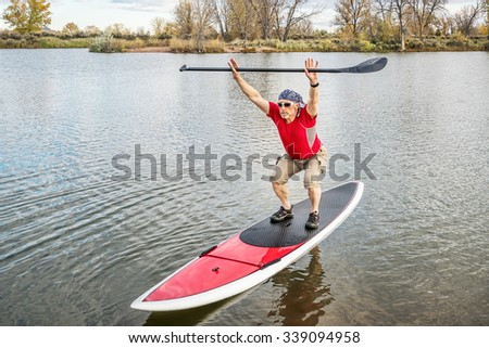 senior male paddler stretching and warming up on a paddleboard before paddling workout on a lake in Colorado - stock photo