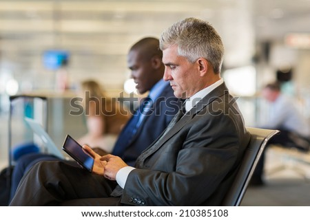 senior male passenger at airport using tablet computer while waiting for his flight - stock photo