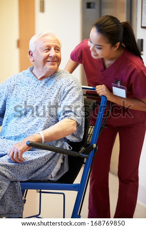 Senior Male Patient Being Pushed In Wheelchair By Nurse - stock photo