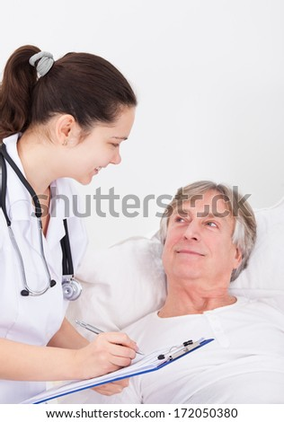 Senior Male Patient Looking At Doctor Writing On Clipboard - stock photo