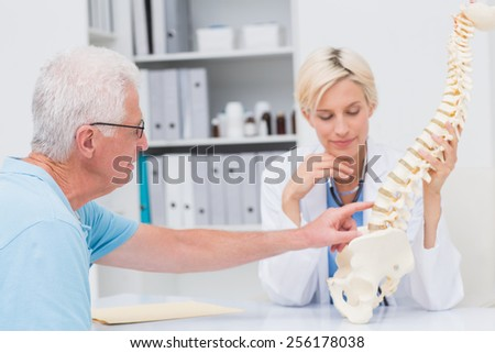 Senior male patient showing spine problems to female doctor in clinic - stock photo