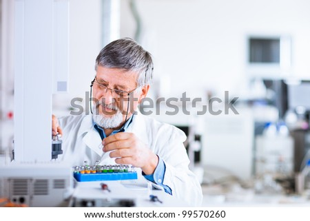 senior male researcher carrying out scientific research in a lab using a gas chromatograph (shallow DOF; color toned image) - stock photo