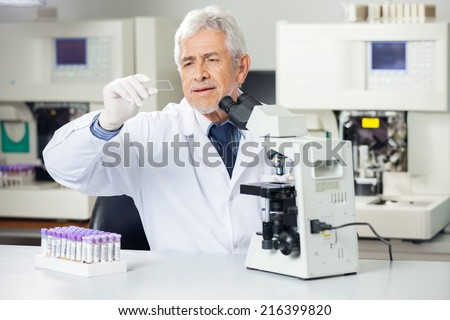 Senior male scientist analyzing microscope slide in medical lab - stock photo