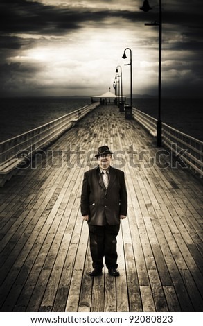Senior Male Standing On A Pier Promenade With Wooden Planks And A Clearing Stormy Sky In The Distance, Photograph Taken Shorncliffe Pier, Queensland, Australia - stock photo