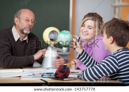 Senior male teacher and students looking at planetarium model at desk in classroom - stock photo