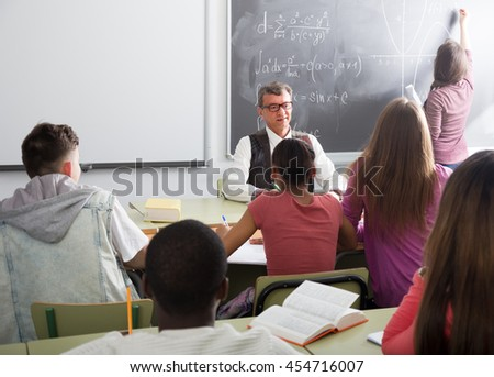 Senior male teacher near the chalkboard asking students at the math lesson