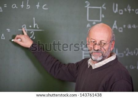 Senior male teacher teaching mathematics while pointing at blackboard in classroom - stock photo