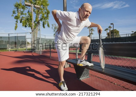 Senior male tennis player with back pain on court - stock photo