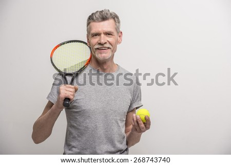 Senior male trainer with tennis racket and tennis. - stock photo