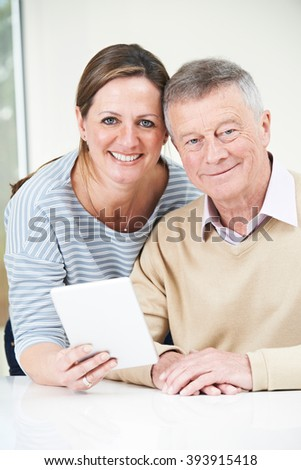 Senior Man And Adult Daughter Looking At Digital Tablet Together - stock photo