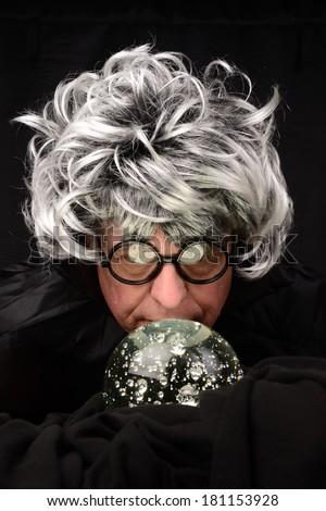 Senior man and crystal ball/Mystic and Crystal Ball/Man gazes into a crystal ball - stock photo