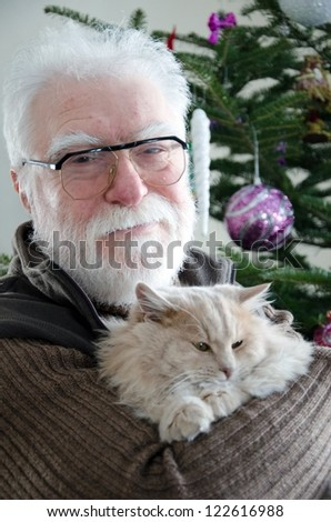 senior man and his cat in front of noel tree - stock photo