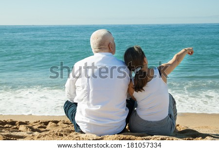 senior man and mature woman together against sea in summer - stock photo