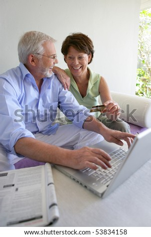 Senior man and senior woman shopping on the web with a laptop computer - stock photo