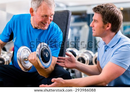 Senior man and trainer at exercise in gym with dumbbell weights - stock photo