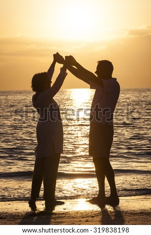 Senior man and woman couple holding hands dancing at sunset or sunrise on a deserted tropical beach  - stock photo