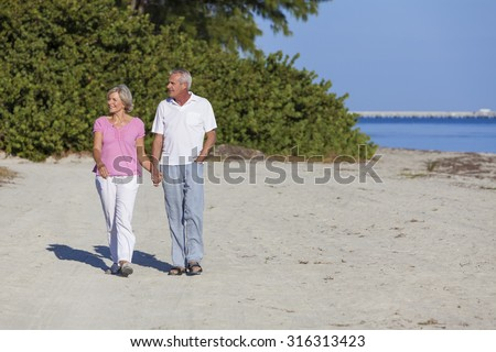 Senior man and woman couple holding hands walking on a deserted beach