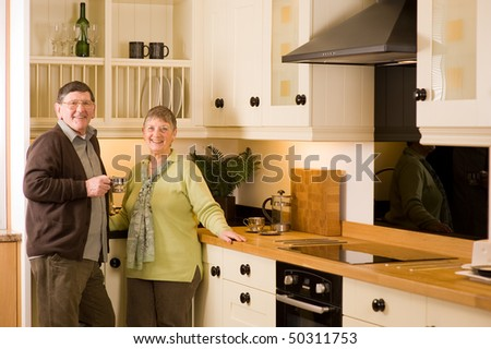 Senior man and woman couple laughing and talking together in modern kitchen - stock photo