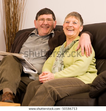 Senior man and woman couple laughing together sitting on sofa in lounge - stock photo