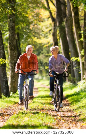 Senior Man and woman exercising with bicycles outdoors, they are a couple - stock photo