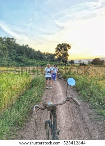 Senior Man and woman exercising with old classic bicycles at the rice fields during the harvest season with rural road in The North of Thailand, Southeast Asia, they are a couple