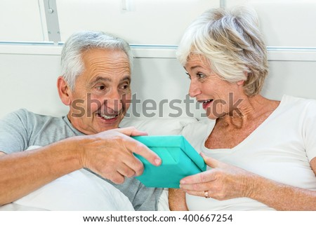 Senior man and woman holding gift box on bed at home - stock photo