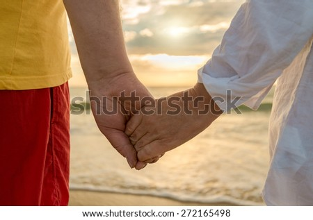 Senior man and woman holding hands of each other at the beach - stock photo