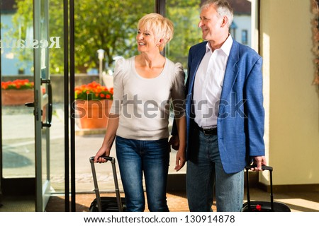 Senior man and woman - married couple - arriving at Hotel with their luggage - stock photo