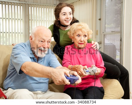 Senior man and woman play video games while their granddaughter looks on.