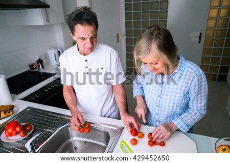 Senior man and woman preparing breakfast. Sunny morning.