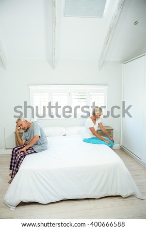 Senior man and woman sitting on bed in bedroom at home - stock photo