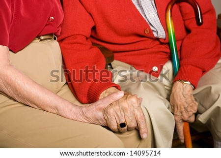 Senior Man and Woman Sitting Together Holding Hands.  Emphasis on Holding Hands and Being Together. - stock photo