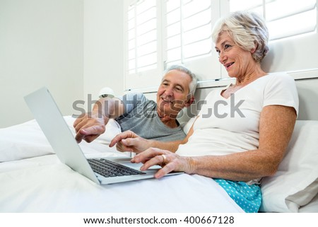 Senior man and woman using laptop on bed against window at home - stock photo