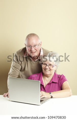 Senior man and woman using laptop whilst looking happy - stock photo