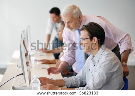 Senior man and young man in front of a desktop computer