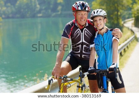 Senior man and young woman on road bike. Copy space - stock photo