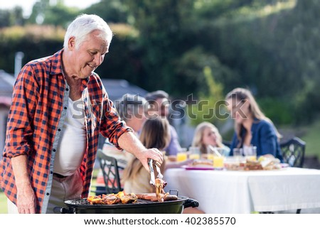 Senior man at barbecue grill while family having lunch in the garden - stock photo
