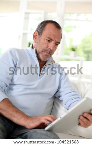 Senior man at home using electronic tablet