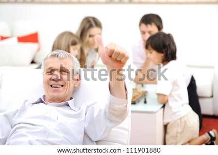 Senior man at home with family in background - stock photo