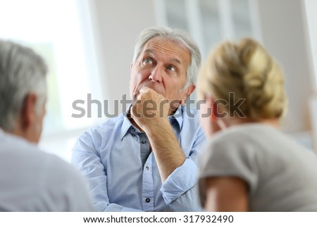 Senior man attending meeting with group therapist - stock photo
