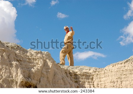 Senior man beckoning from high up on a cliff. To view all 4 images from this series keyword: khaki/man