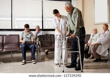 Senior man being helped by female nurse to walk the Zimmer frame with people sitting in hospital lobby - stock photo